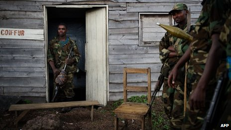 M23 rebels stand outside a small wooden shack in the village of Kanyarucinya, 6km from Goma, in eastern DR Congo, 18 November 2012