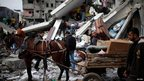 Palestinians load their belongings onto a horse cart after an Israeli air strike on a house in Gaza City. 18/11/2012
