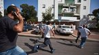 Israelis run for cover as a siren warning of incoming rocket sounds in the southern city of Ashkelon 18/11/2012