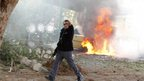 Israeli police officer in front of burning car in Ashkelon (18 Nov 2012)
