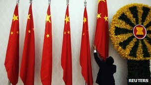 An official adjusts Chinese flags before Chinese Premier Wen Jiabao arrives for the 21st Asean and East Asia summits in Phnom Penh, 18 Nov 2012