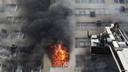 Firefighters work to extinguish the fire from a 15-floor commercial building after it broke out in central Delhi