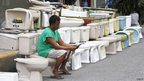 A worker takes a break and reads a newspaper sitting on a second-hand toilet bowl he is selling, on display along a street in Paco, metro Manila
