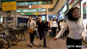 Israelis in Tel Aviv run for cover during a rocket attack on Sunday