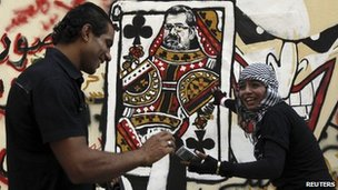 Youths admire a mural on Cairo's Mohammed Mahmoud street showing Mohammed Mursi's head on a queen of clubs playing card