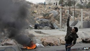 A Palestinian youth throws a stone towards Israeli forces at the Qalandia checkpoint, West Bank. Photo: 19 November 2012