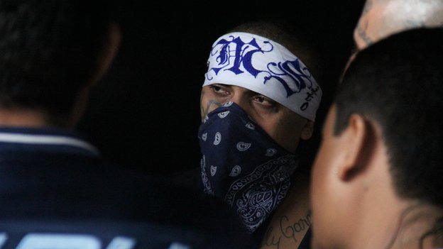 A Mara Salvatrucha leader with a bandana covering his face