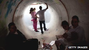 Israelis in Nitzan take cover in a large concrete pipe during a rocket attack from the Gaza Strip on 19/11/12