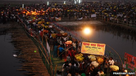 Tens of thousands of pilgrims gather on the banks of the Ganges  to pray to the setting sun