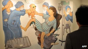 A painting portraying Park Geun-Hye of South Korea's New Frontier Party giving birth to her own father and late strongman, Park Chung-Hee, at a Seoul gallery, 20 November 2012