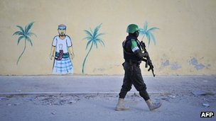 A Nigerian policeman working with the African Union Mission in Somalia walks by a painted image on a newly built wall during a foot patrol near Lido beach in Somalia's capital, Mogadishu