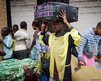 Kadogo Ombeni stands near the Rwandan border with Congo with a suitcase on his head