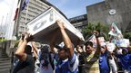 Protesters carry an empty coffin