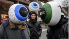 Demonstrators wearing giant fake eyes