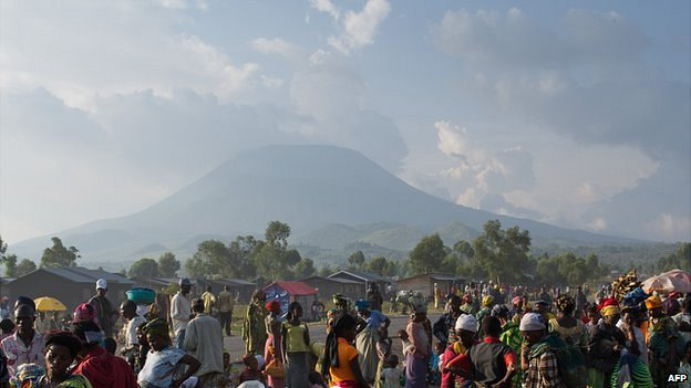 People at a roadside on the outskirts of Goma with the Nyiragongo volcano on the horizon - eastern DR Congo, 3 August 2012