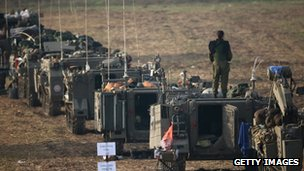 Armoured personnel carriers wait in a staging area