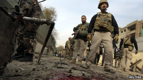 Foreign security personnel inspect the site of the suicide bomb attack in Kabul