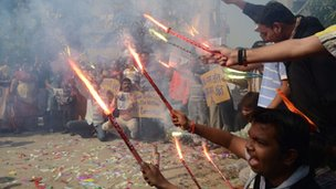 Indians in Ahmedabad hold lit fireworks while celebrating the hanging of Ajmal Qasab