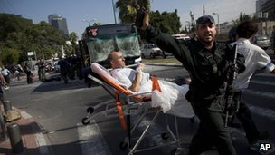 Israeli rescue workers and paramedics carry a wounded person from the site of a bombing in Tel Aviv, Israel