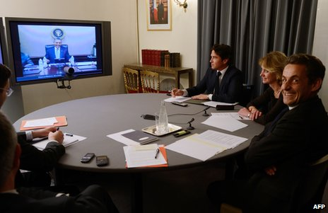 Nicolas Sarkozy (right), then French president, smiles at the Elysee Palace during a video link-up with his US counterpart, Barack Obama, 12 April 2012