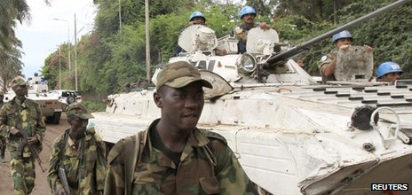 A UN armoured vehicle drives past rebels patrolling a street in Goma in the eastern Democratic Republic of Congo, soon after capturing the city from the government army - 20 November 2012