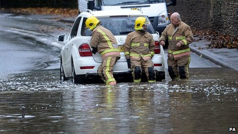 A fire service crew removes a car from floodwater near Tetbury,  Gloucestershire