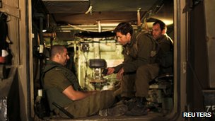 Israeli soldiers sit in an Armoured Personnel Carrier (APC) at a staging area outside the northern Gaza Strip November 21, 2012.