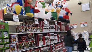 Shoppers walk past festive items in Wal-Mart