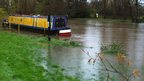 A canal barge appears to be floating in a field