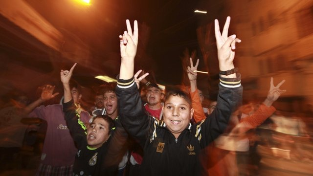 Palestinian boys celebrate the ceasefire, which they say is a victory over Israel