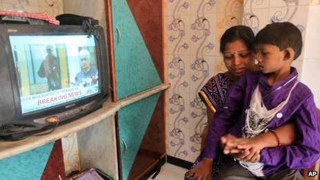 Karuna, wife of a victim of the 2008 Mumbai attacks Thakur Budha Vaghela, breaks down as she watches with her son Neeraj the news of Mohammed Ajmal Kasab&quot;s execution, in Mumbai, India, Wednesday, Nov. 21