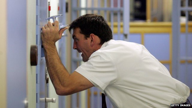 A police officer inspects a cell at a police station custody suite