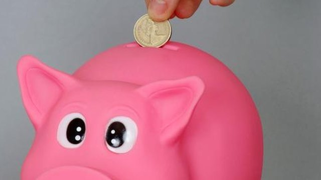 Sterling pound coin saved in a pink piggy bank