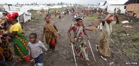 Internally displaced people walk through Mugunga camp, near Goma on 21 November 2012