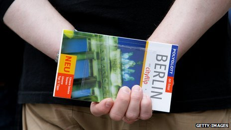 A man holding a Berlin travel guide behind his back