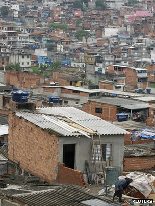 A man works on a house under construction in the Brasilandia slum in Sao Paulo