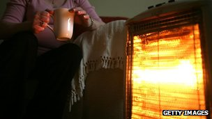 Pensioner in front of heater