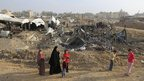 Women and children walk past tents near bombed smuggling tunnels near Rafah (22 Nov 2012)