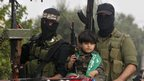 A Palestinian boy and militants of the Izzedine Al-Qassam Brigades, the armed wing of Hamas, attend funerals of five Hamas militants in Mugharka village, central Gaza Strip (22 Nov 2012)