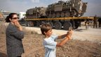 "A woman and her son look at Israeli reserve soldiers and army vehicles as they depart the Gaza border area near Israel""s border with the Gaza Strip (22 Nov 2012)"