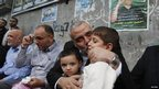 Senior Hamas leader Ismail Haniyeh kisses the son of Hamas military chief Ahmed Jaabari (pictured on poster at R), who was killed by an Israeli air strike, as he consoles the family in Gaza City (22 Nov 2012)