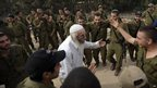 An Ultra Orthodox man from the Jewish Breslov sect dances as Israeli troops prepare to leave a deployment area near the Israel-Gaza Strip border (22 Nov 2012)