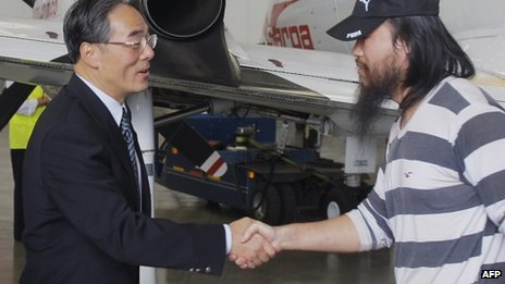 Chinese ambassador Wang Xiao shakes hands with one of four freed workers at the airport in Bogota, on November 22