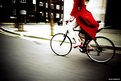 Red-coated woman on bike