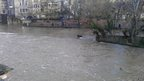 Swollen waters around Pulteney Weir in Bath