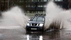 Car drives through flood in Paisley, Renfrewshire