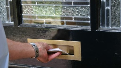 Postman posting letters through letterbox