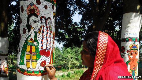 Madhubani art being painted on a tree