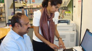 Volunteer Sahar Rai helps library user Krishnapillai Preamkumar
