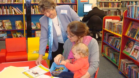 Volunteer Vera Wall with library user Sabrina Atkins and her daughter